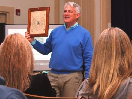 A historian holds up an antique compass rose print at our Antiques Roadshow event