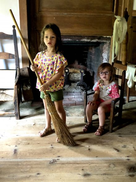 Two little girls sit by the fireplace enjoying the tour of the Nye house