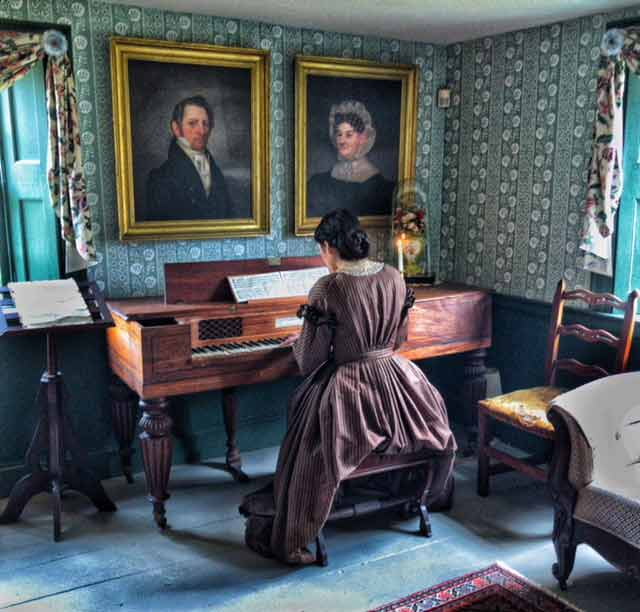 A woman in pilgrim period costume sits and plays the piano in the Nye homestead