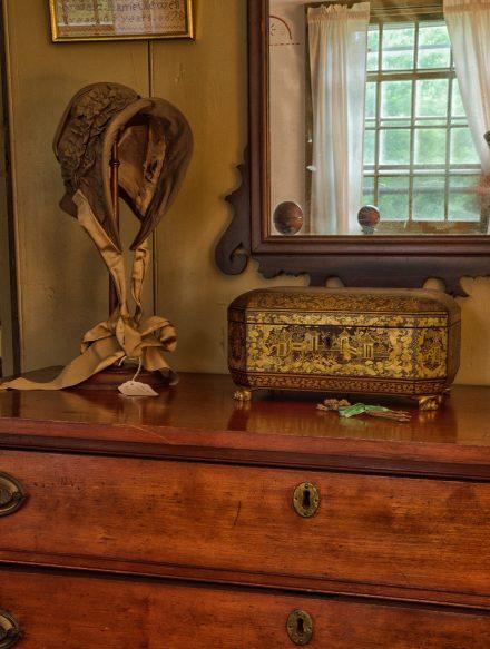 A pilgrim's bonner and jewelry box sitting on an antique dresser below a mirror