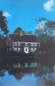 An illustration of the Nye homeastead with blue sky and reflection in the pond